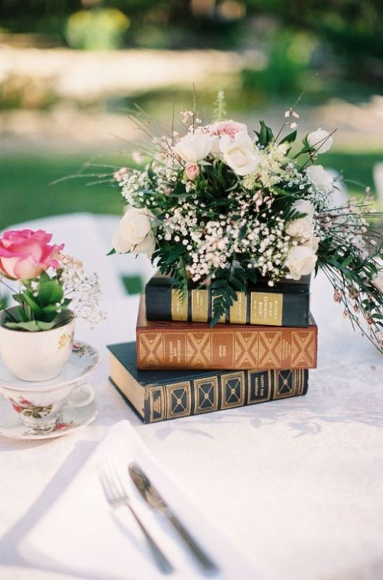 Beautiful Garden Wedding Centerpiece Idea With A Stack Of Books Plus A Lush Floral Arrangement On Top
