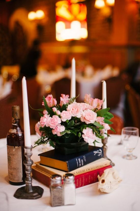 Beautiful Vintage Wedding Centerpiece With A Stack Of Books And A Black Vase With Pink Flowers And Candles Around