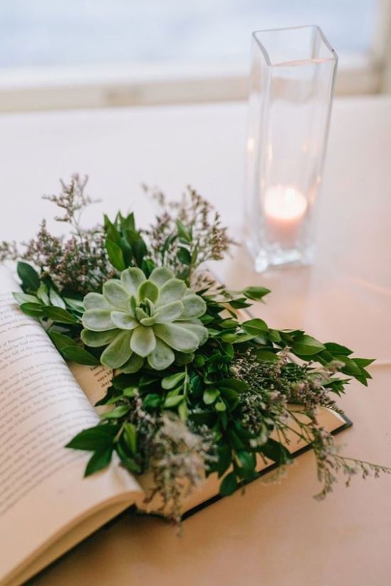 Chic And Refreshing Wedding Centerpiece Idea With An Opened Book With Lush Greenery Plus Blooms And A Large Succulent