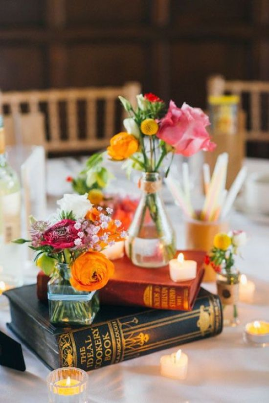 Cool Fresh And Bold Wedding Centerpiece With Books And Candles And Mini Vases With Just Some Blooms In Bold Colors