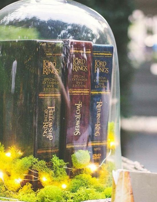 Cool Wedding Centerpiece Idea For A Themed Wedding With A Large Cloche With Moss And LED Lights And LOTR Books