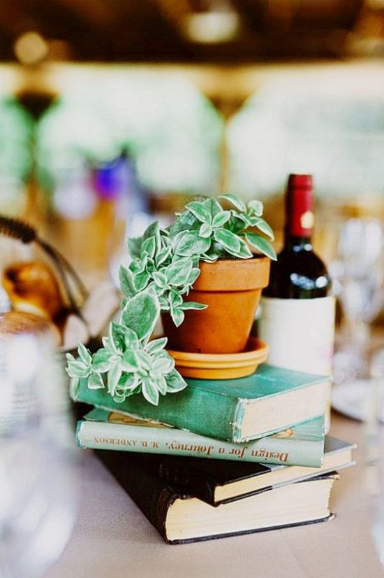 Easy DIY And Very Budget-Friendly Wedding Centerpiece Idea With A Stack Of Books With Potted Cascading Greenery On Top