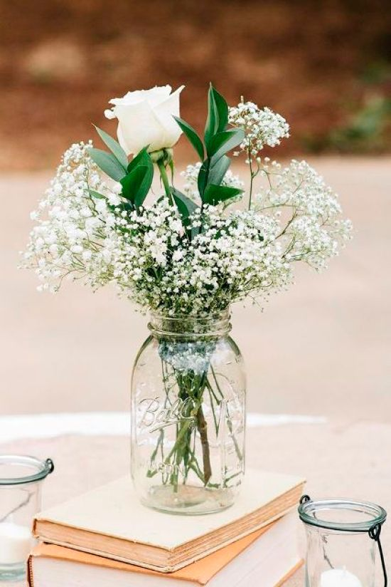 Rustic And Vintage Wedding Centerpiece Idea With Vintage Books With A White Floral Arrangement On Top