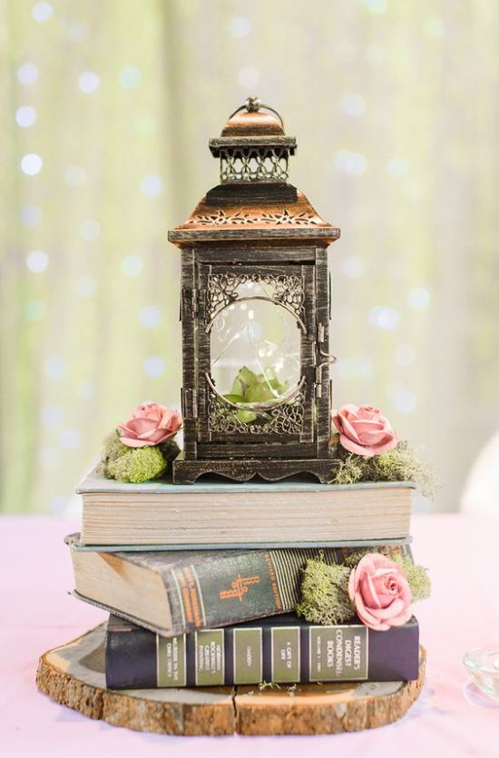 Rustic And Vintage Wedding Centerpiece With A Stack Of Books Plus Moss With Pink Roses And A Large Vintage Lantern With A Succulent Inside