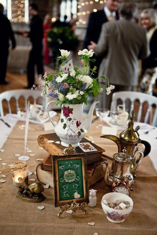 Wedding Centerpiece Idea With A Stack Of Books And Vintage Coffee Pots Plus A Coffee Pot With A Floral Arrangement And Some Figurines Around