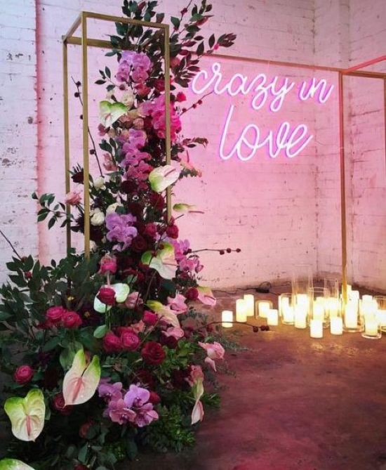 A Beautiful Wedding Ceremony Space With Candles An Arch Lush Florals In Red Burgundy And Pink And A Pink Neon Sign
