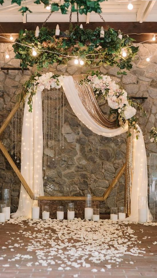 A Glam Hexagon Wedding Arch Decorated With Lush Pastel And Neutral Blooms Greenery Candles And A White And Gold Curtain With Lights Inside Plus Petals Around