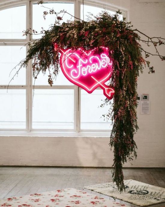 A Lush Greenery And Bright Pink Blooms Wedding Arch With A Large Pink Neon Heart Is A Stunning Modern Idea