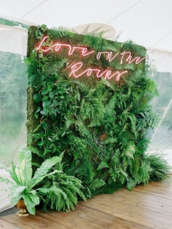 A Lush Greenery Wall With A Red Neon Sign For A Very Fresh And Cool Wedding Decor Idea