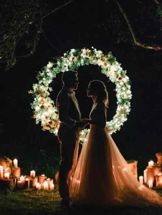 A Mini Round Wedding Arch Fully Made Of Greenery And Blooms And Lights Inside It Plus Candles All Around For A Night Ceremony