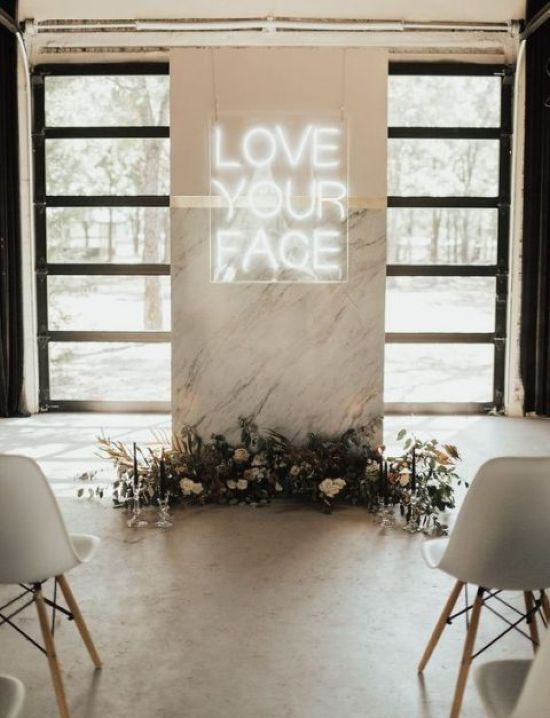 A Minimalist Wedding Ceremony Space Done With A Marble Altar Decorated With Dried Leaves Blooms And A Neon Sign
