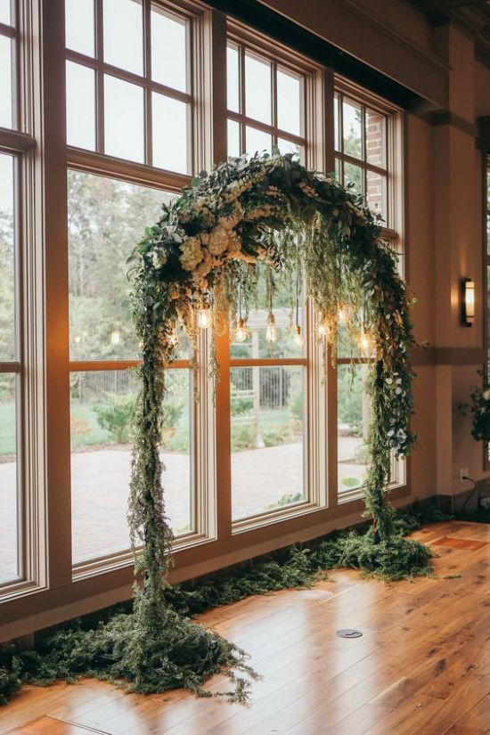 A Rounded Wedding Arch Fully Covered With Greenery And White Blooms And Some Bulbs Hanging Down For An Accent