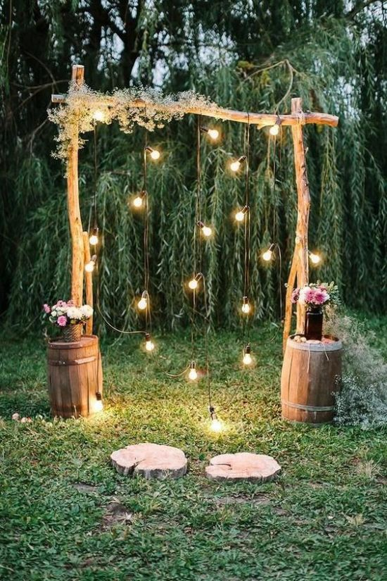 A Rustic Wedding Arch Of Branches Decorated With Baby's Breath With Bulbs Hanging Down And Some Blooms In Barrels