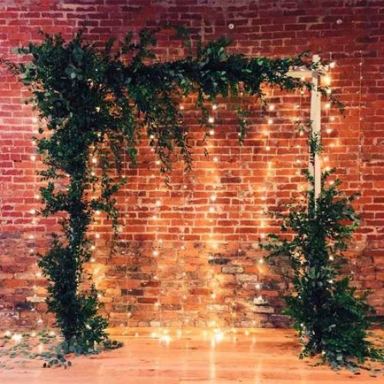 A Simple Indoor Wedding Arch Decorated With Lush Greenery And With String Lights That Will Highlight Your Couple