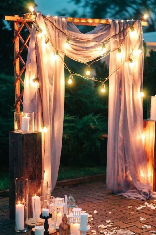 A Simple Wedding Arch Draped With Pink Fabric String Lights With Lots Of Candles And Candle Lanterns Around It