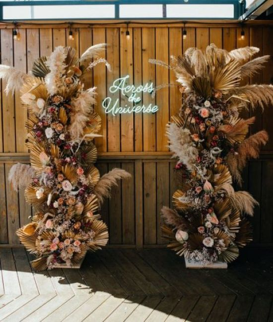 A Stunning Boho Wedding Altar With Lush Blooms And Dried Fronds And Pampas Grass And A Neon Sign