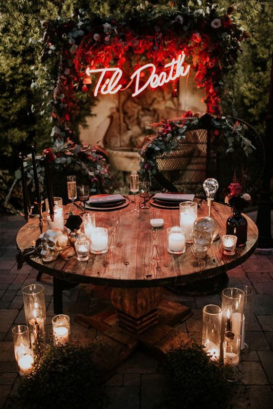 A Stylish Idea For A Halloween Wedding A Neon Sign Spruced Up With Lush Red Blooms And Greenery