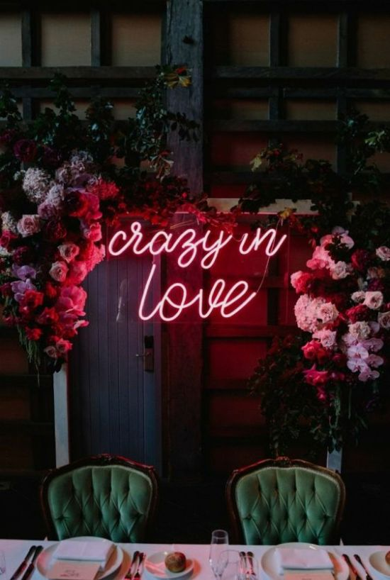 A Wedding Arch Moved To The Reception To Spruce It Up With Its Bold Florals And A Bold Neon Sign