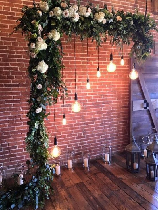 An Indoor Wedding Arch Done With Greenery And Neutral And Pastel Blooms Hanging Bulbs And Candles In Candle Lanterns