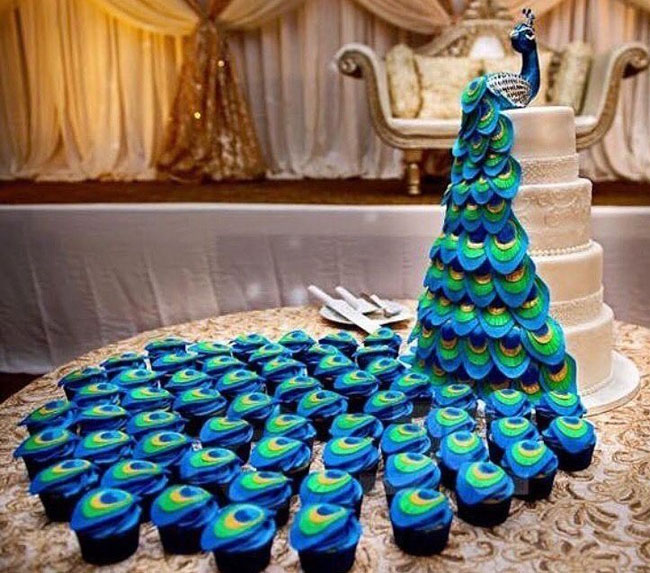Three Tiered Peacock Wedding Cake With Blue Cupcakes